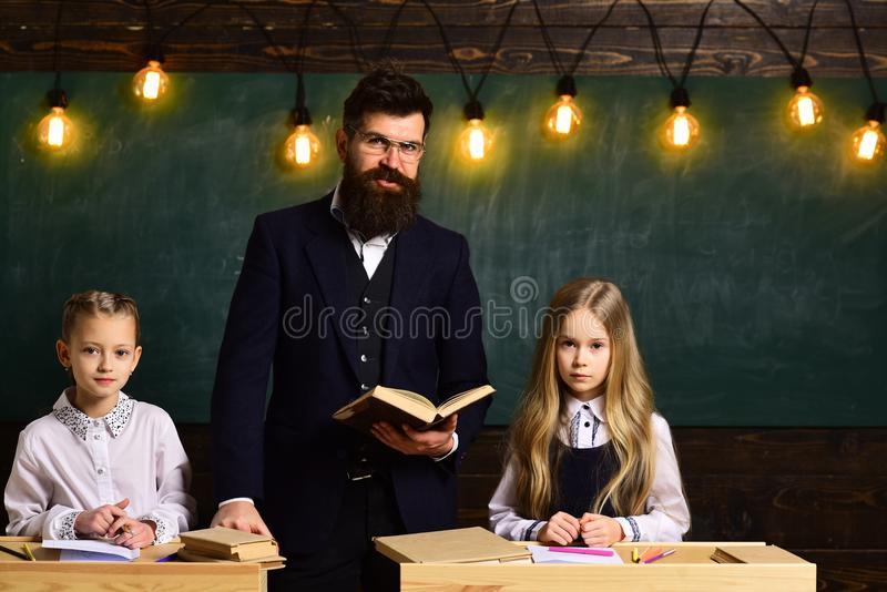 High school or college students studying and reading together in library. Kids need to do homework on regular basis. Teacher drawing with her little student at stock photo