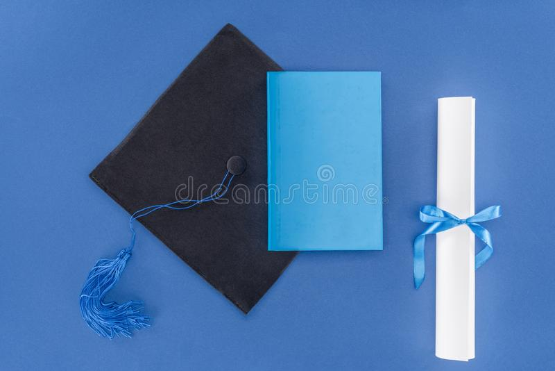 High school concept with diploma and graduation cap. Isolated on blue royalty free stock photos