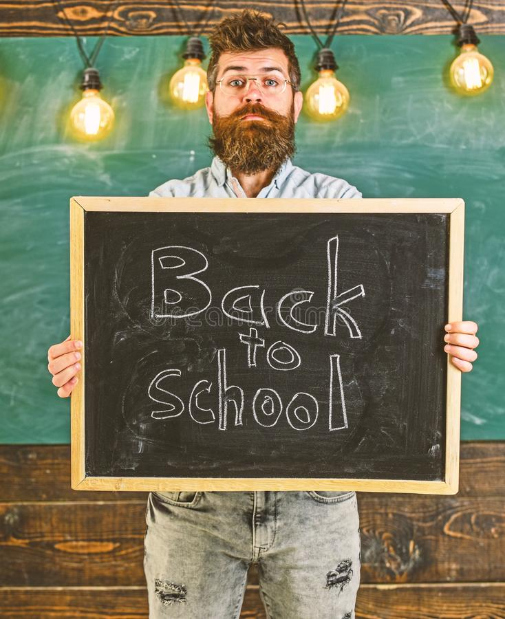 High school concept. Teacher in eyeglasses holds blackboard with title back to school. Man with beard and mustache on. Calm face welcomes students, chalkboard royalty free stock images