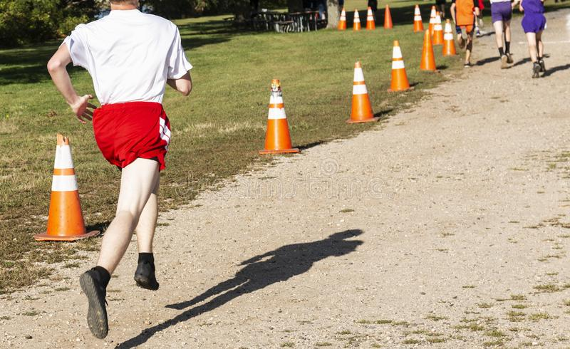 High school cross country runner chasing the leader to the finish line stock images
