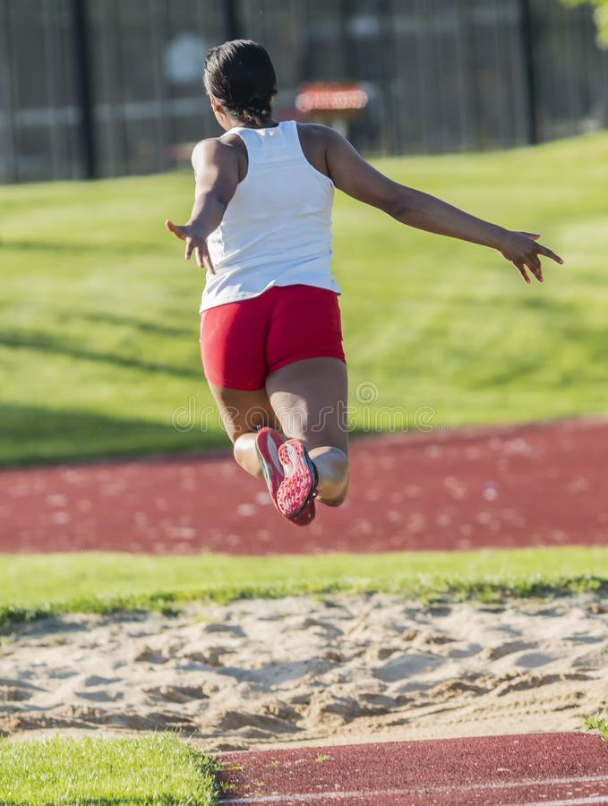 Long triple jumper in the air from behind stock photos