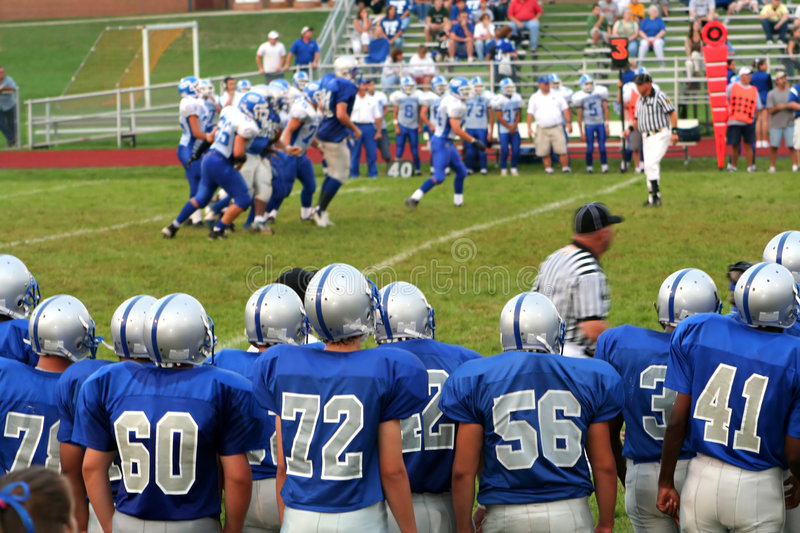 High School Football 4. High school football team standing on the sidelines of a field, watching a game in progress stock photography