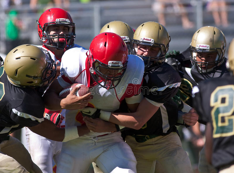 High School Football Player Being Tackled During a Game. A football player from Mills High School in California, about to be tackled during a game against Harbor stock photo