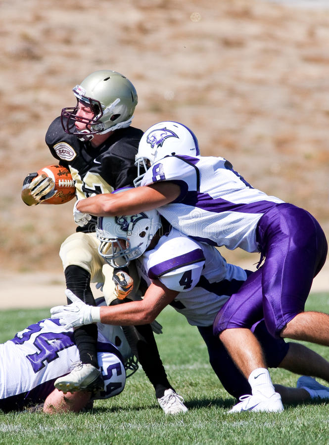 High School Football Player Being Tackled During a Game. A football player from Scotts Valley High School in California, about to be tackled during a game royalty free stock photography