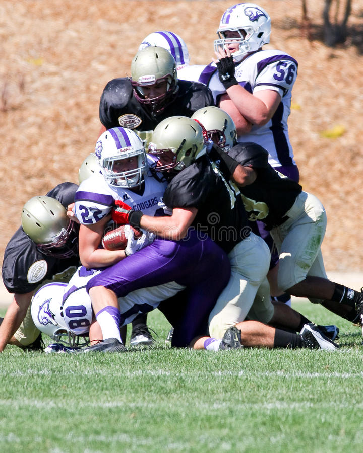High School Football Player Being Tackled During a Game. A football player from Spanish Springs High School in California, being tackled during a game against royalty free stock photos