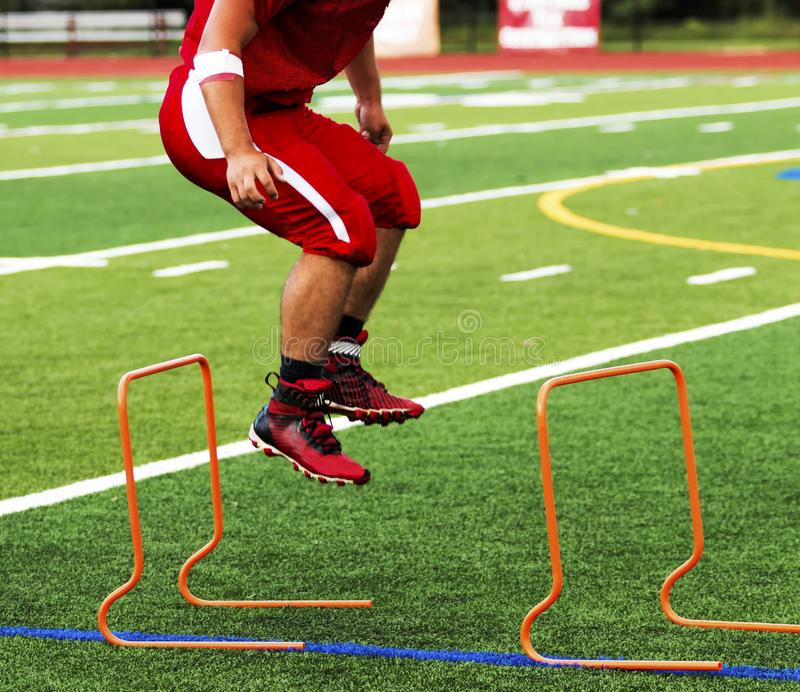 High School Football player jumping over mini hurdles. A high school football player jumping over orange hurdles during pre season practice on a gree turf field royalty free stock photos