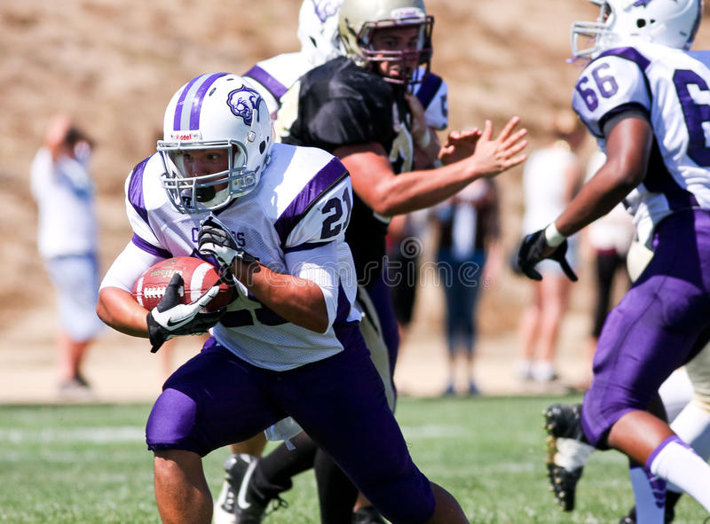 High School Football Player Running with the Ball During a Game. A football player from Spanish Springs High School in California, running with the ball during a royalty free stock photo