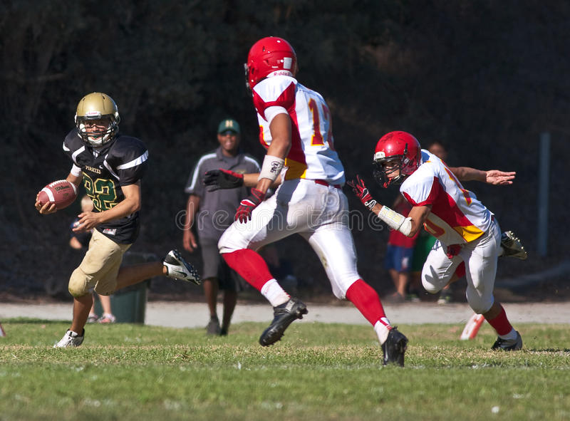 High School Football Player Running with the Ball. A football player from Harbor High School in California, runs down the field with the ball during a game stock images