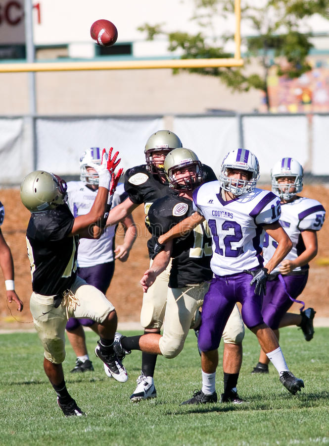 High School Football Players in Action During a Game. A football player from Scotts Valley High School in California, reaching to catch the ball during a game royalty free stock photography