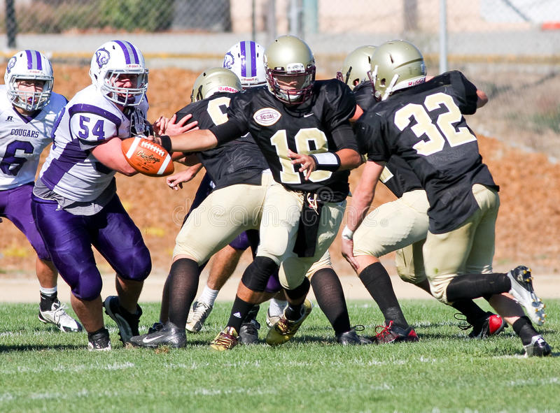 High School Football Players in Action During a Game. The Quarterback from Scotts Valley High School in California, hands-off the football during a game against stock photo