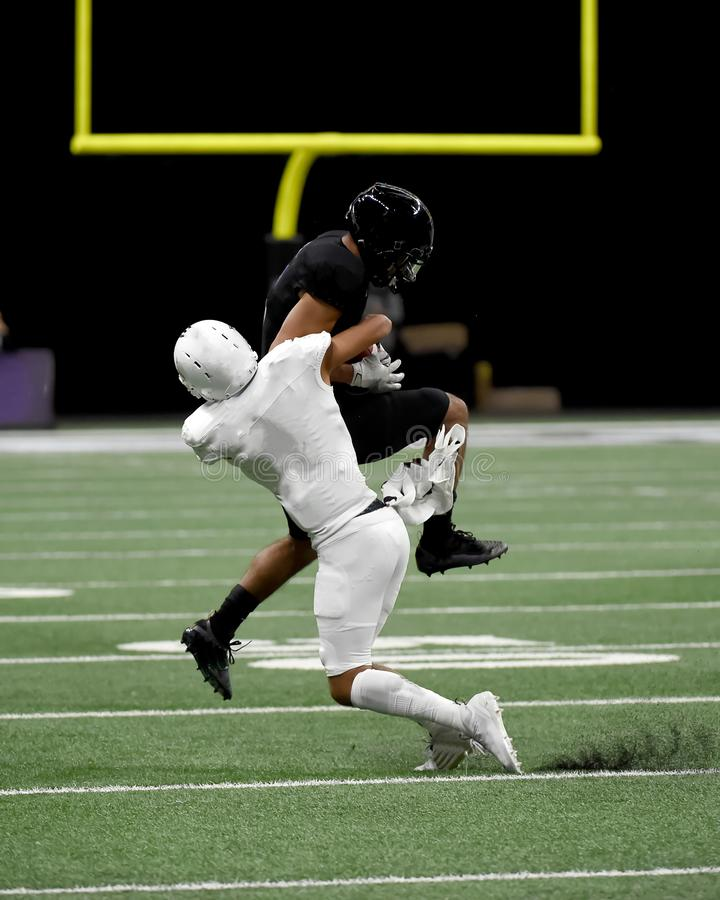 Great action photos of high school football players making amazing plays during a football game. High School football players making great plays during games in royalty free stock photos