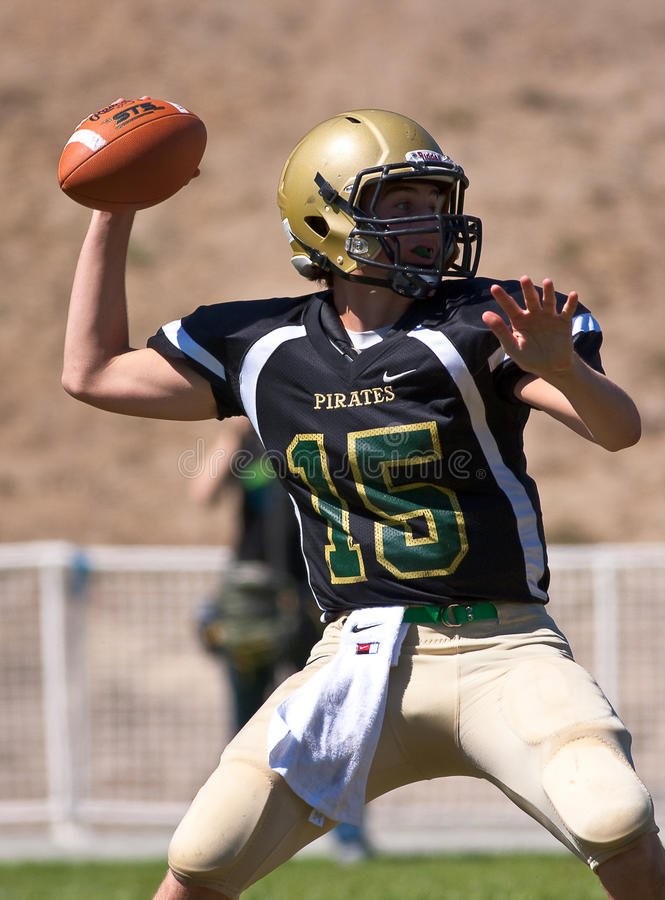 High School Football Quarterback Passing the Ball. A football player from Harbor High School in California, throws a pass during a game against Mills High School stock image