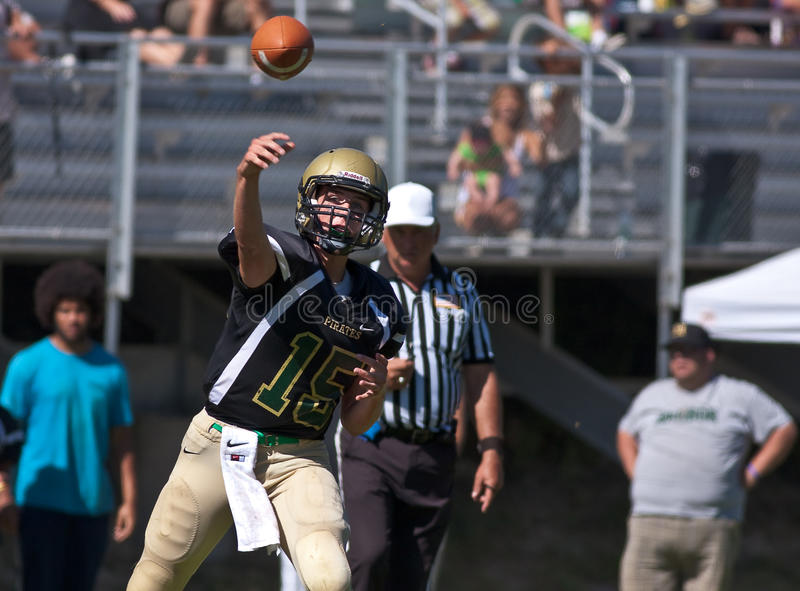 High School Football Quarterback Passing the Ball. A football player from Harbor High School in California, throws a pass during a game against Mills High School royalty free stock image