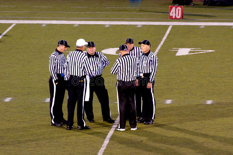 High School Football Referees. Referees conferring at a high school football game royalty free stock photography