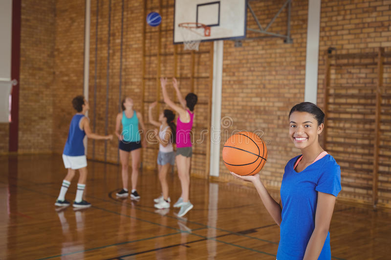 High school girl holding a basketball while team playing in background stock photography