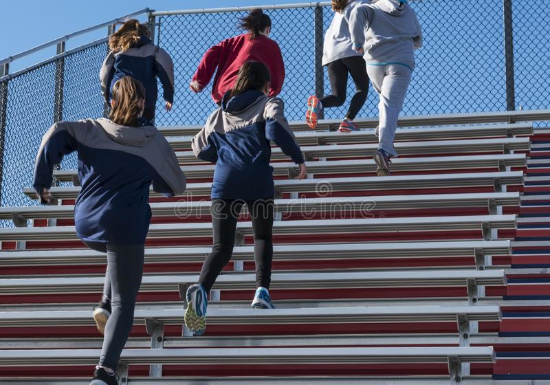 High school girls running up bleachers on a cold sunny day. A high school girls track and field team running up the bleachers on a cool fall afternoon stock photo