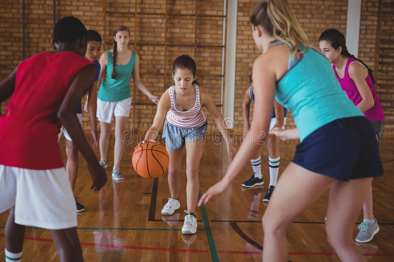 High school kids playing basketball in the court. Determined high school kids playing basketball in the court royalty free stock images