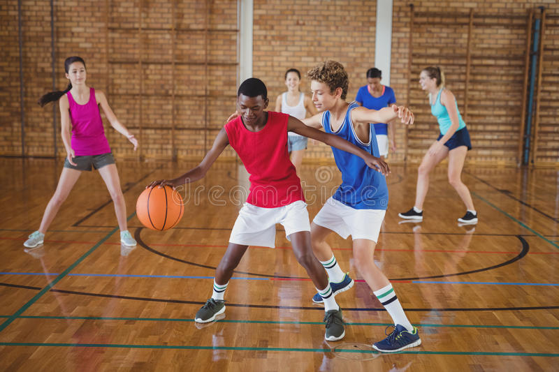 High school kids playing basketball in the court. Determined high school kids playing basketball in the court royalty free stock photography