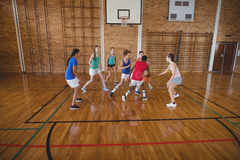 High school kids playing basketball in the court. Determined high school kids playing basketball in the court stock images