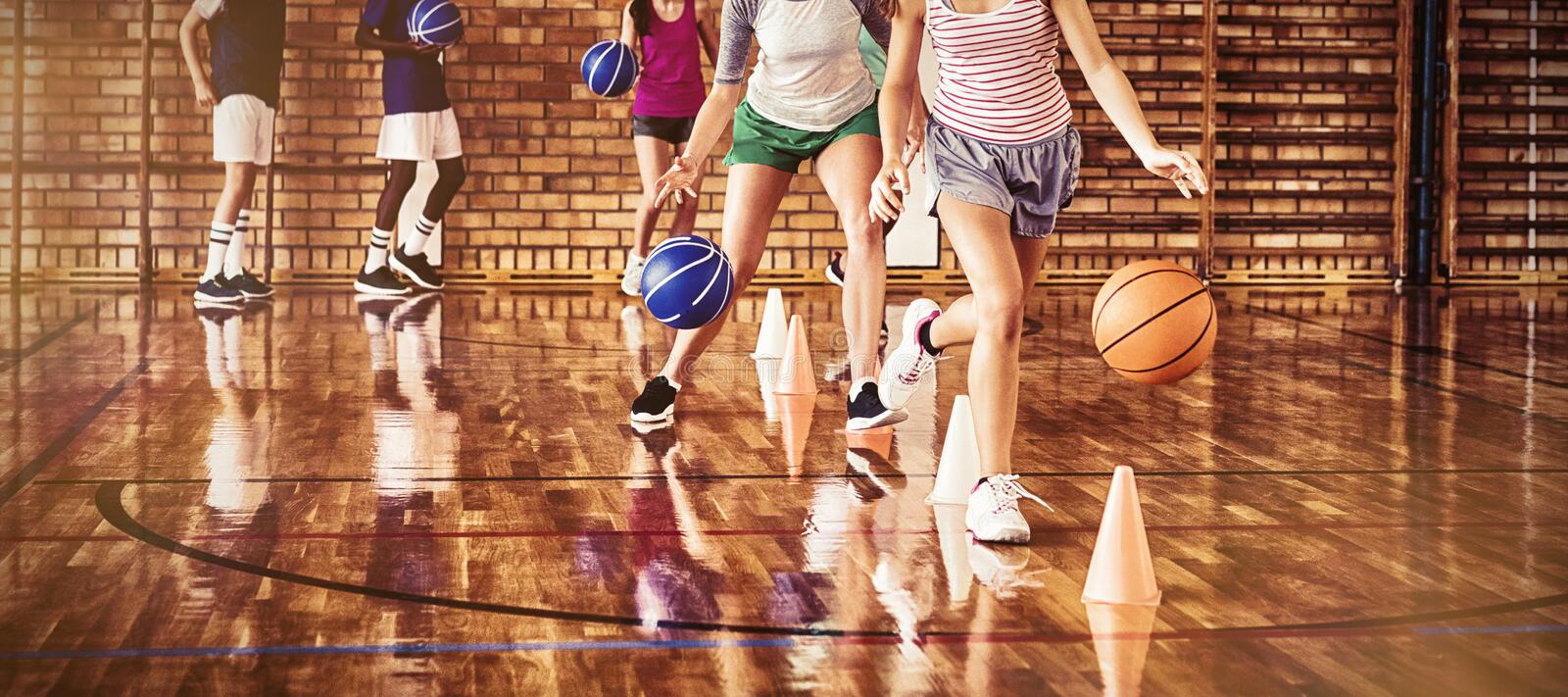 High school kids practicing football using cones for dribbling drill. In the court royalty free stock image