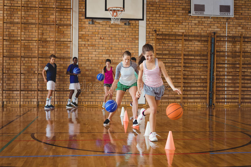 High school kids practicing football using cones for dribbling drill royalty free stock photography