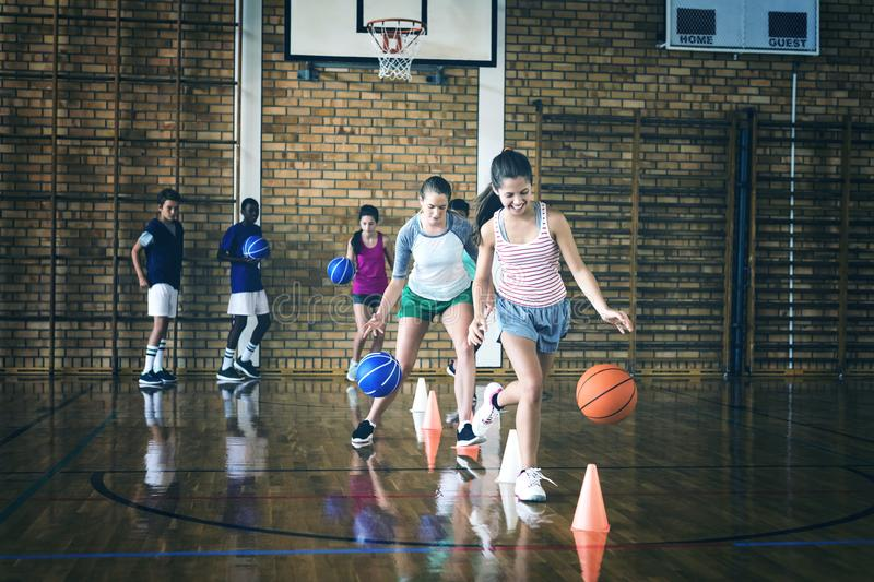 High school kids practicing football using cones for dribbling drill. In the court royalty free stock images