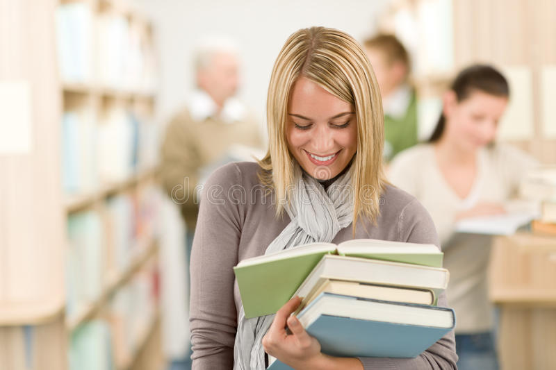 High school library - happy student with book. High school library - happy female student with book read stock images