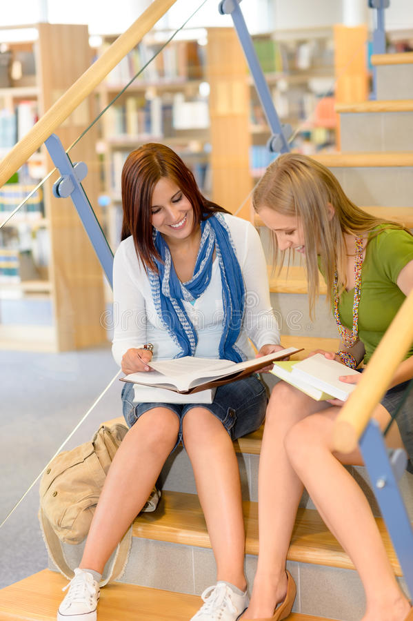 High school library students sitting on stairs stock photography