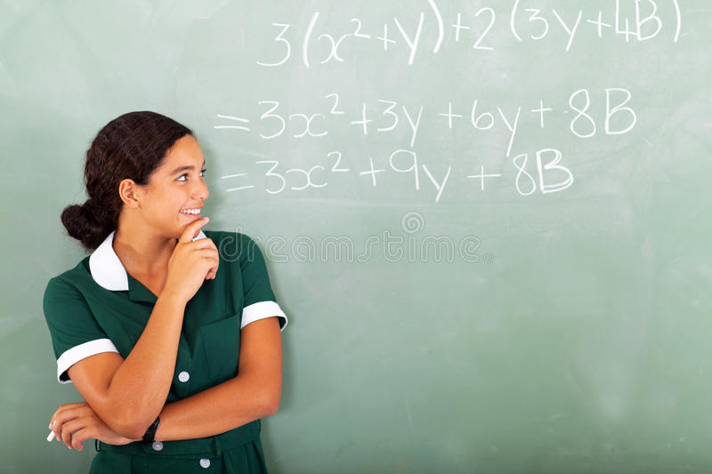 High school maths. Happy female high school student in classroom looking at maths writing on the blackboard royalty free stock photo
