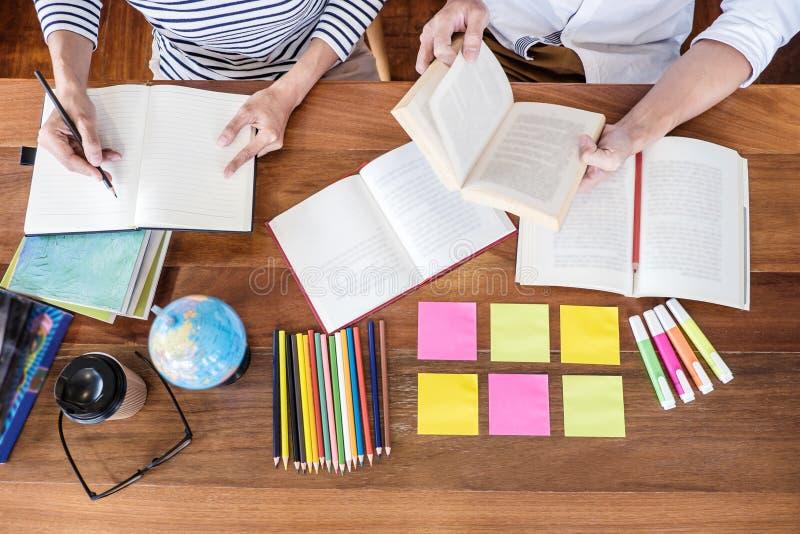 High School ou grupo de estudante universitário que senta-se na mesa na biblioteca que estuda e que lê, fazendo a preparação da p fotografia de stock royalty free