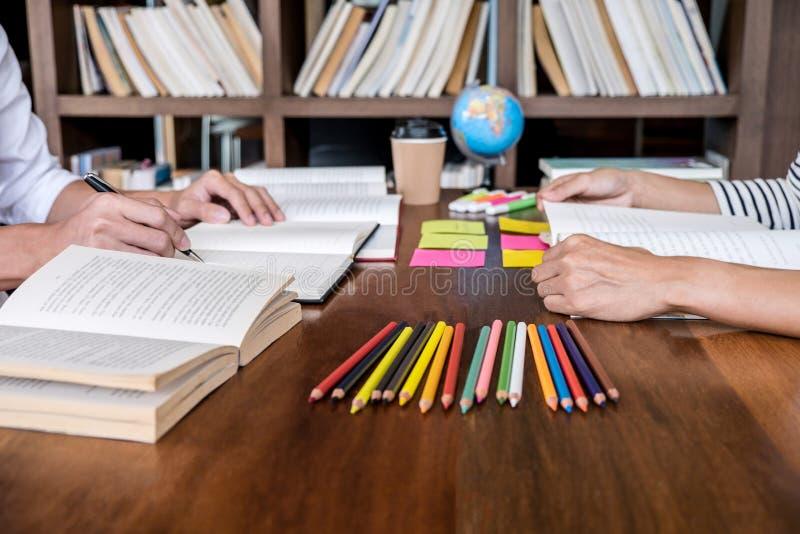 High School ou grupo de estudante universit?rio que senta-se na mesa na biblioteca que estuda e que l?, fazendo a prepara??o da p fotos de stock