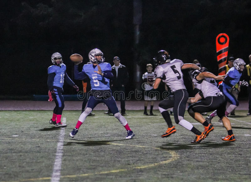 High school quarterback raises ball for a pass; opponents charge. Corvallis, Oregon, October 2016: High school quarterback prepares to throw. Opponents attempt royalty free stock photography