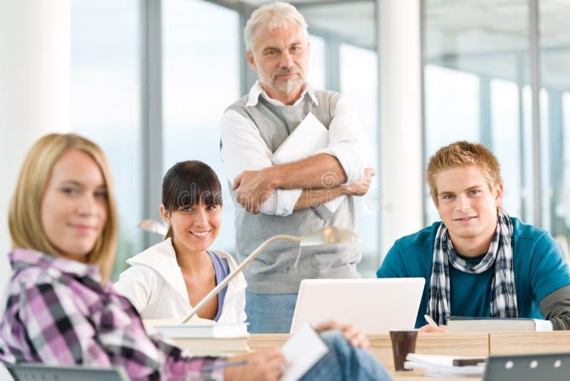 High School secundaria - tres estudiantes con el profesor maduro imagen de archivo