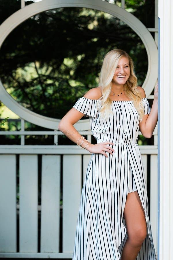 High School Senior Photo of Blonde Caucasian Girl Outdoors in Romper Dress stock images