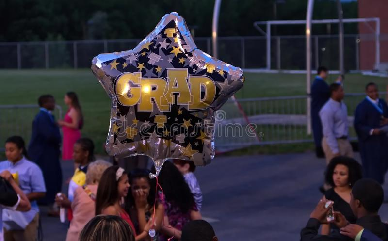 High School Seniors Crying Farewells After Graduation. Middletown, CT USA. Jun 2013. High school graduation balloon in the foreground of happy and celebrating stock photos
