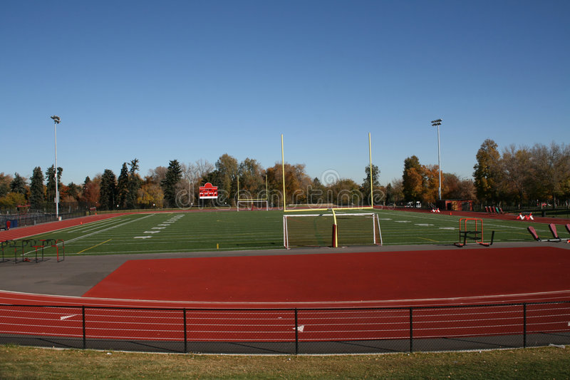 High school sports field. High school running track and football field stock photo