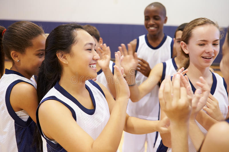 High School Sports Team Celebrating In Gym. Close Up Of High School Sports Team Celebrating In Gym Looking Happy royalty free stock image