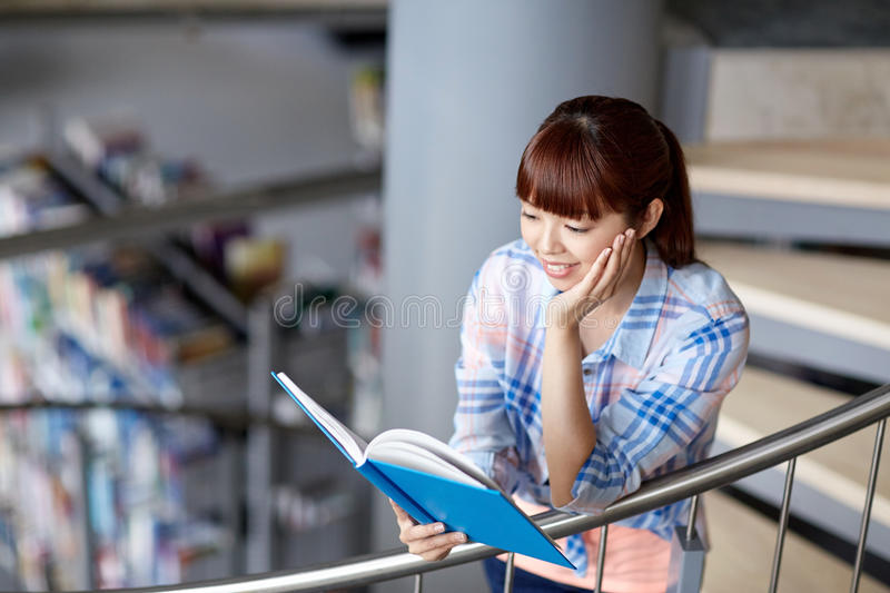 High school student girl reading book at library royalty free stock photo