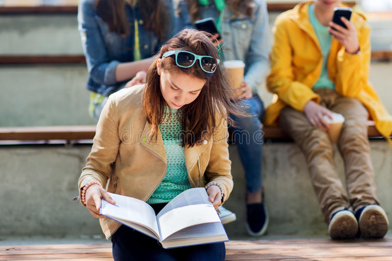 High school student girl reading book outdoors stock photo