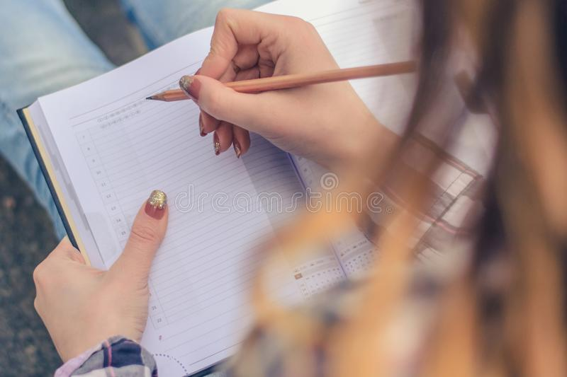 Close up photo of girl`s hands writing composition in her diary. High school student pupil university book note pad notebook read imagine dream dreamy people stock photography