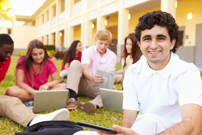 High School Students Studying Outdoors On Campus. Happy High School Students Studying Outdoors On Campus Using Laptops And Digital Tablets stock photography