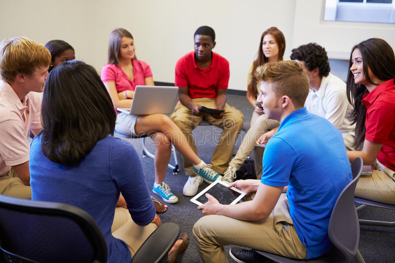 High School Students Taking Part In Group Discussi. On Sitting On Chairs Using Digital Tablets And Laptops royalty free stock photos