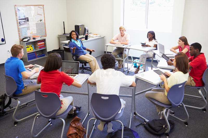 High School Students Taking Part In Group Discussi. On Sitting In A Circle Using Laptops And Digital Tablets royalty free stock photos