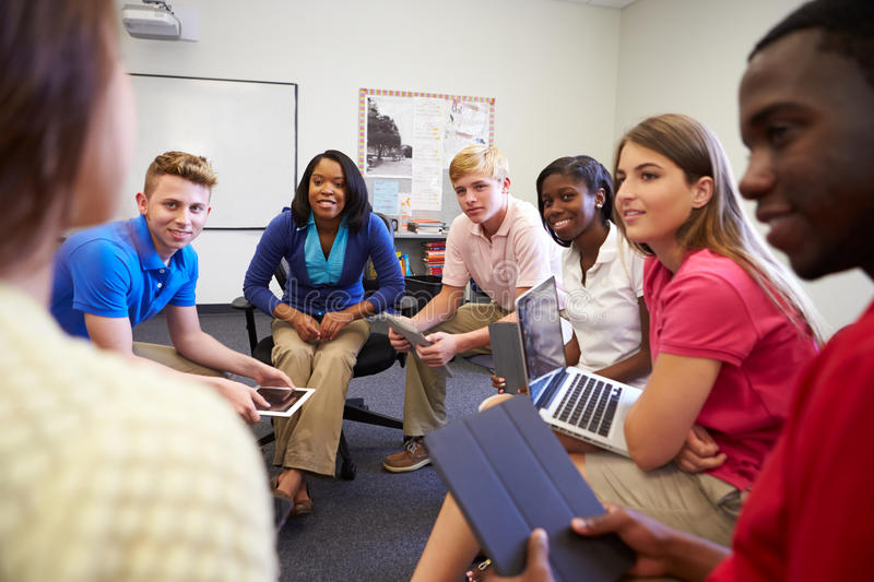 High School Students Taking Part In Group Discussi. On Using Laptops And Digital Tablet royalty free stock image
