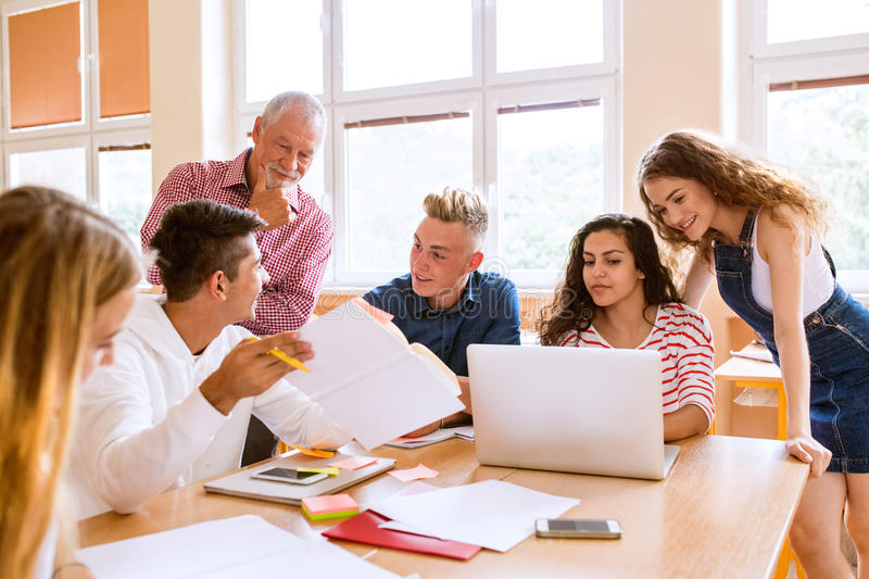 High school students and teacher with laptop. stock images