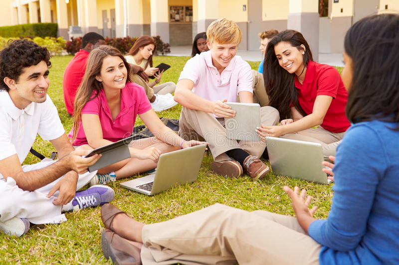 High School Teacher Sitting Outdoors With Students On Campus. Using Digital Tablets And Laptops royalty free stock photos