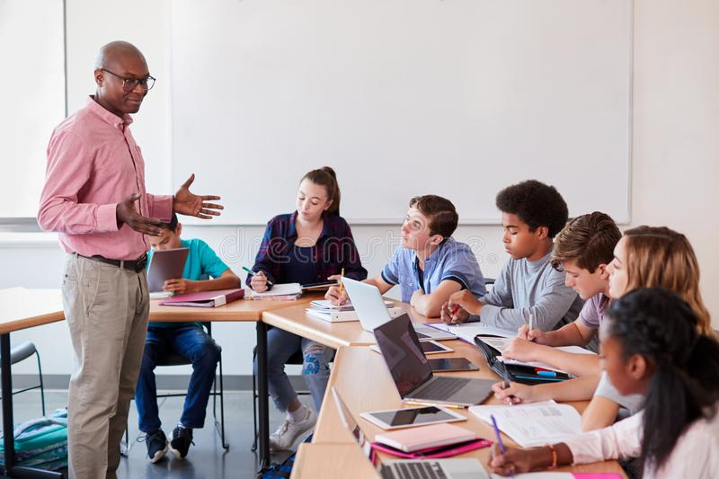 High School Teacher Talking To Pupils Using Digital Devices In Technology Class royalty free stock photo