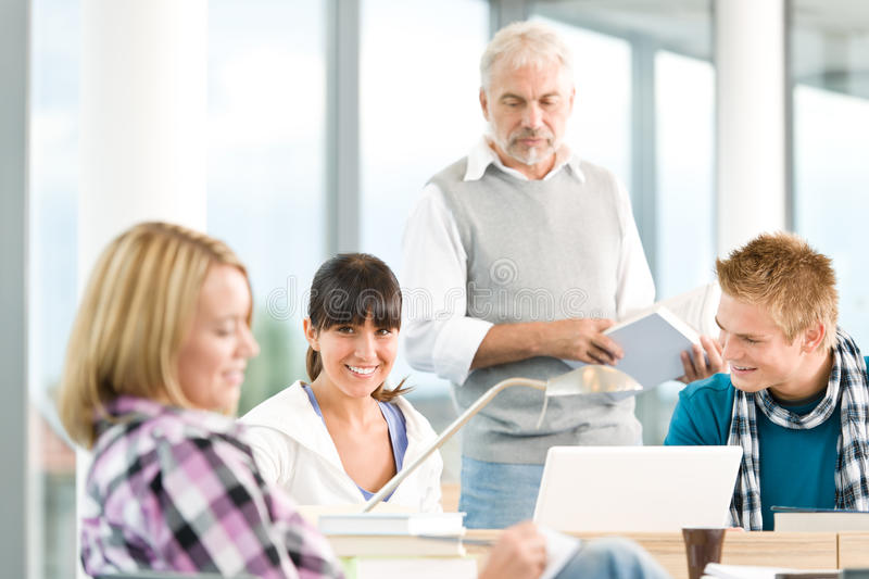 High school - three students with mature professor royalty free stock image
