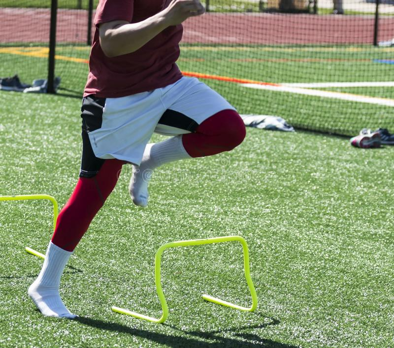 Runner performing speed drills with no shoes on. A high school track and field athlete is performing a speed and agility drill over yellow mini banana hurdles on royalty free stock photography