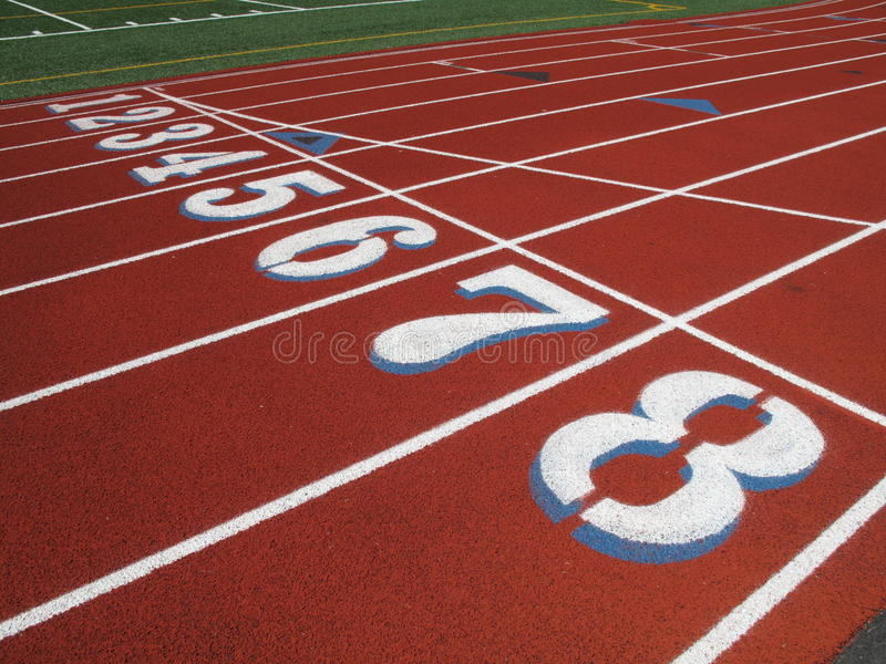 High School Track Starting Line. A track at a high school. Rubberized surface with graphics for the runners and lanes painted on stock photo